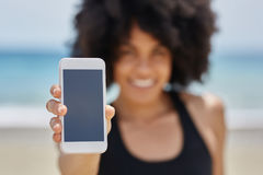 Happy afro american girl holding brand new smartphone Stock Image