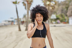 Happy afro american girl listening music on beach Royalty Free Stock Photography