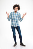 Happy afro american man with curly hair. Full length portrait of a happy afro american man with curly hair standing isolated on a white background Stock Image