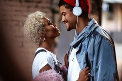 Happy Afro American man in heaphones and his dark skinned female with curly hairdo stand close to each other, look stock image