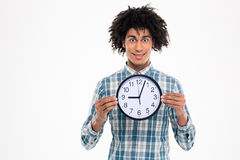 Happy afro american man holding wall clock Stock Photo