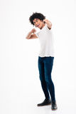 Happy afro american man pointing fingers at camera. Full length portrait of a happy afro american man pointing fingers at camera isolated on a white background Royalty Free Stock Photos