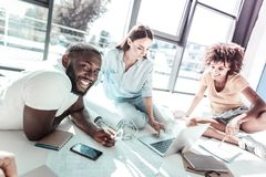 Happy Afro-American man posing on camera. Lets prepare. Relaxed international female keeping smile on her face and sitting on the floor while staring at computer royalty free stock photography