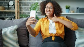 Happy Afro-American teenager taking selfie with thumbs-up hand gesture at home. Happy Afro-American teenager is taking selfie with thumbs-up hand gesture at home stock video footage