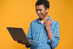 Happy Afro American teenager working with laptop. Royalty Free Stock Photos