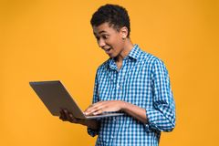 Happy Afro American teenager working with laptop. Royalty Free Stock Photo