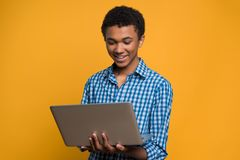 Happy Afro American teenager working with laptop. Royalty Free Stock Images