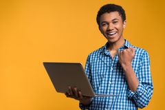 Happy Afro American teenager working with laptop. Stock Photo