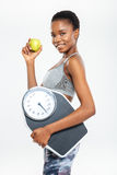 Happy afro american woman holding scales and apple Stock Photo