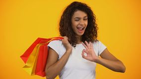 Happy Afro-American woman holding shopping bags and showing ok gesture, sale. Stock footage stock video footage