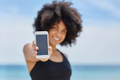 Happy afro american woman holding smartphone. Portrait of happy afro american woman holding smartphone Royalty Free Stock Photos