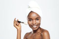 Happy afro american woman with makeup brush and towel Stock Images