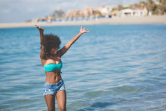 Happy afro american woman standing in water rising hands Royalty Free Stock Image