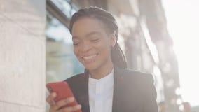Happy afro businesswoman using smartphone standing on the street near business centre. Black Stylish. Dreadlocks. Female stock video