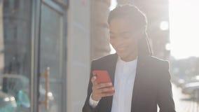 Happy afro businesswoman using smartphone standing on the street near business centre. Black Stylish. Dreadlocks. Female stock video footage