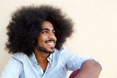 Happy afro man sitting and looking away Royalty Free Stock Image