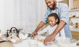 Happy bakers concept. Happy afro men and his child daughter rolling up dough together, having fun. Happy bakers concept, copy space stock image