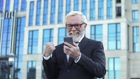 Happy aged businessman receiving good news, making yes-gesture, app for business royalty free stock photo