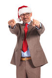 Happy aged businessman wearing santa claus cap pointing his fing Royalty Free Stock Photo