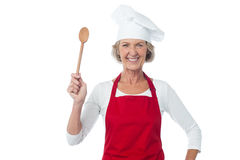 Happy aged chef holding wooden spoon Stock Image