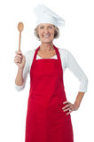 Happy aged chef holding wooden spoon Stock Photography