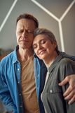 Happy aged couple embracing with gentle hands. Enjoyable meeting. Waist up portrait of happy excited aged women and men tenderly embracing together with gentle stock photography