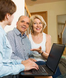 Happy aged couple talking with employee with laptop Stock Photo