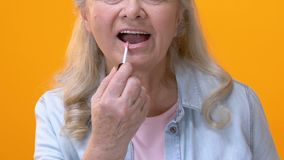Happy aged female applying pink lip gloss, preparing for event, face make-up. Stock footage stock video footage