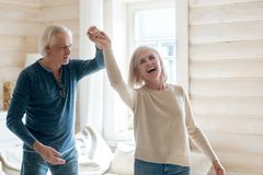 Happy aged husband and wife dancing at home stock image