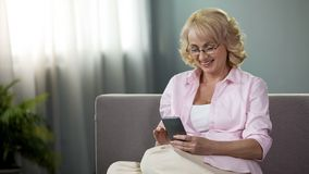 Happy aged lady in glasses viewing photos on smartphone, relaxing on sofa, app stock photography