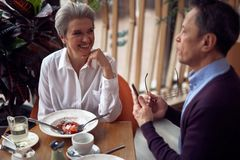 Happy aged lady and man having discussion. Enjoyable meetings. Waist up top angle portrait of aged smilig elegant women and gentleman having interesting royalty free stock image