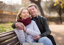 Happy aged lovers on a bench in the park Stock Photography