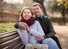Happy aged lovers on a bench in the park Stock Image