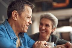 Happy aged man enjoying meeting with beloved lady. Enjoyable meeting. Close up side on portrait of cheerful aged male enjoying meeting in cafe with beloved woman stock image