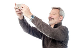Happy aged man taking pictures of themselve Stock Photos