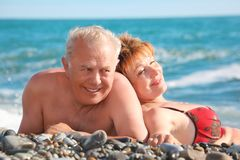Happy aged pair lie on pebble beach stock image