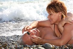Happy aged pair lie on pebble beach stock photos