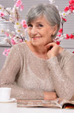 Happy aged woman drinking coffee Stock Photos