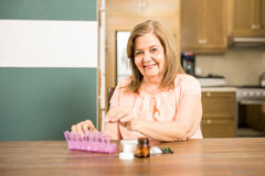 Happy aged woman filling her pill box Stock Image