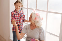 Happy aged woman giving a hair roller to her granddaughter Stock Photography