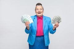 Happy aged woman holding many euro and dollars. Portrait of handsome expressive grandmother in light blue suit with collected gray hair bun hairstyle. Studio royalty free stock photos