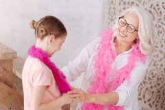 Happy aged woman looking at her granddaughter. You are a beauty. Happy nice aged women wearing a pink feather boa and smiling while looking at her beautiful Royalty Free Stock Image
