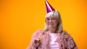 Happy aged woman in pink coat and round glasses celebrating birthday anniversary royalty free stock image