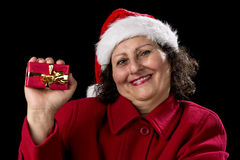 Happy Aged Woman Presenting Red Wrapped Xmas Gift. Smiling female pensioner with red coat and Santa Claus cap is showing a wrapped Christmas present with golden Royalty Free Stock Images