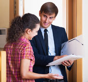 Happy agent with documents. Happy young agent with documents and potential client talking near door Stock Photo