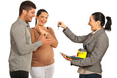 Happy agent giving keys to couple. Happy real estate agent women giving keys to pregnant couple isolated on white background Stock Image