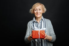 Happy aging pensioner holding box with present in the studio. This s for you. Delighted smiling old woman expressing happiness and holding gift box while royalty free stock image
