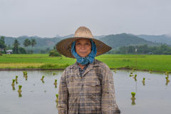 Happy agriculture woman with green field in raining day Stock Photo