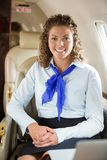 Happy Airhostess Sitting In Private Jet Stock Images