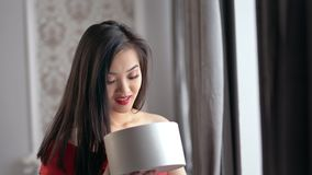 Happy amazed elegant Asian woman opening gift box and smiling at home cozy interior. Happy amazed elegant Asian woman opening gift box and smiling. Charming